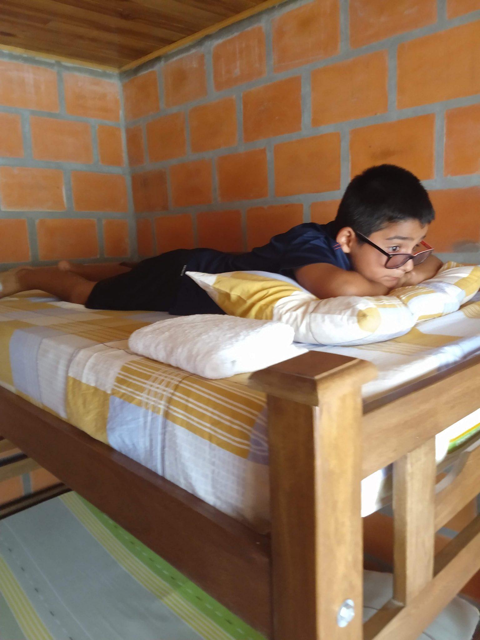 Mateo lying on his bed at Cabanas el Descanso y Zamukia