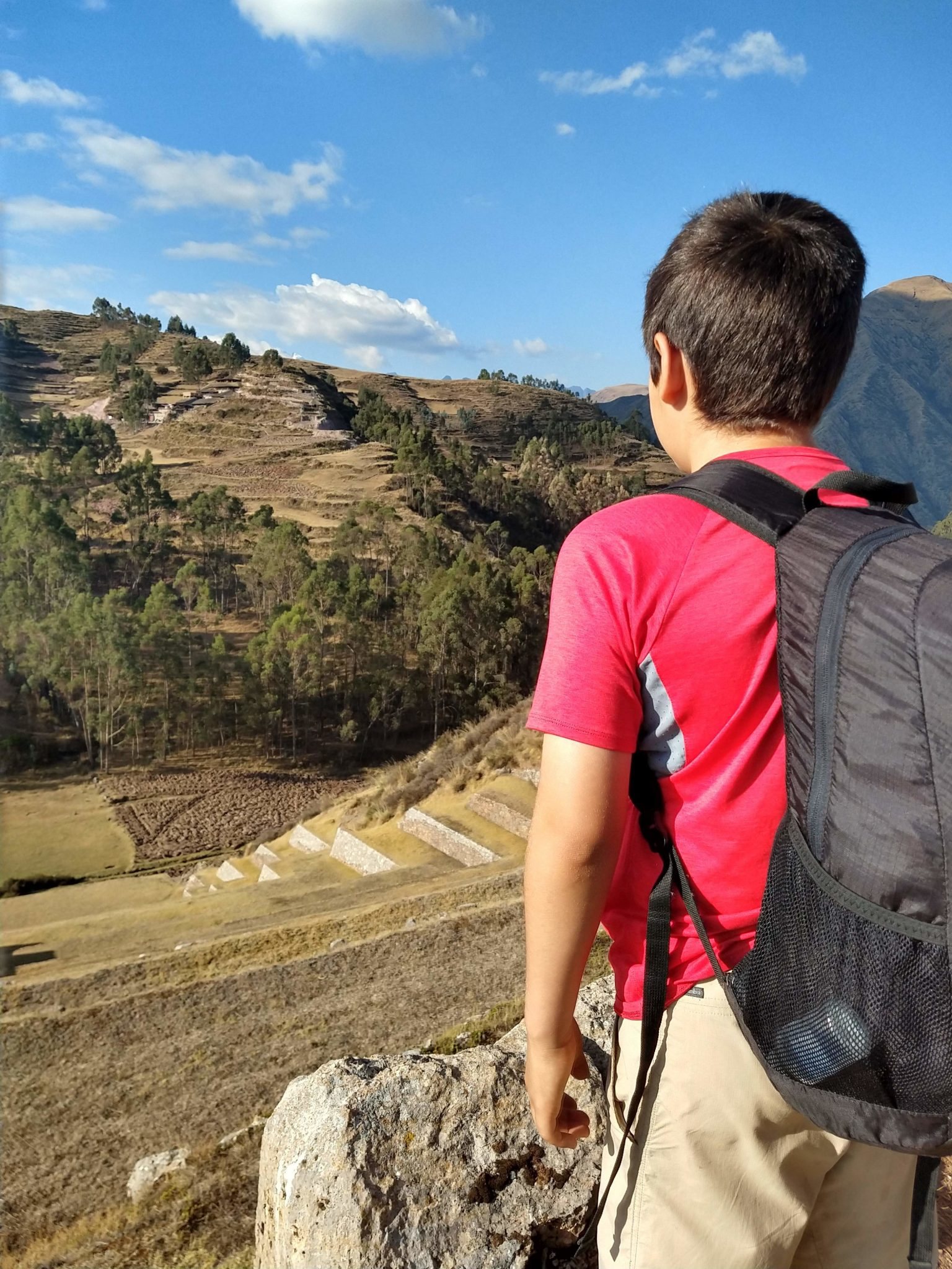 Marco looking at a terrace in Peru wearing a backpack